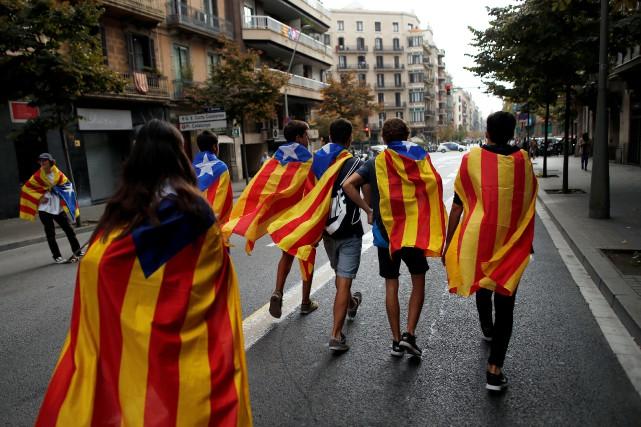 People wrapped in Esteladas (Catalan separatist flags) walk... (REUTERS)