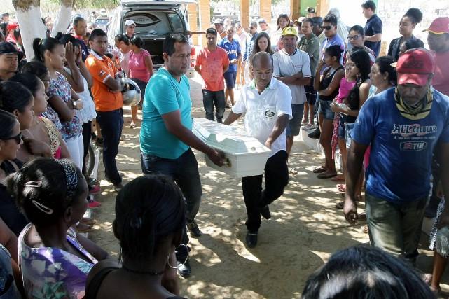 Deux hommes transportent le cercueil de Juan Miguel... (PHOTO ALEX DE JESUS , AFP)