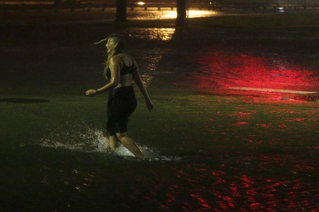 Une femme marche sur une rue inondée à... (Photo Brynn Anderson, Associated Press)