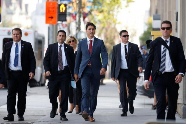 Le premier ministre Justin Trudeau entouré d'agents du... (PHOTO CHRIS WATTIE, REUTERS)