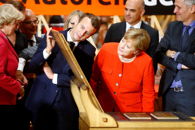 Emmanuel Macron etAngela Merkel visitent le pavillon français... (PHOTO REUTERS)