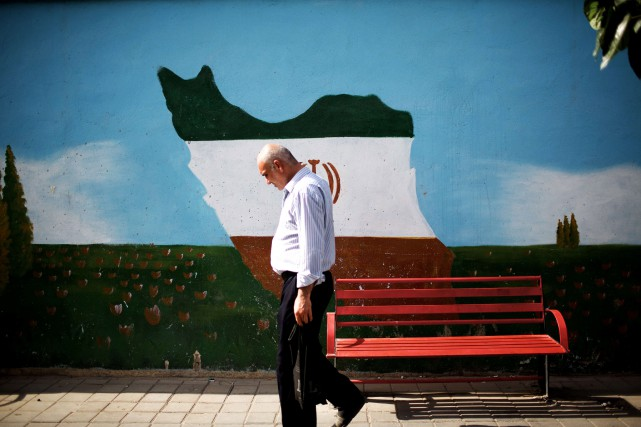 Un homme passe devant une murale dépeignant la... (ARCHIVES AFP)