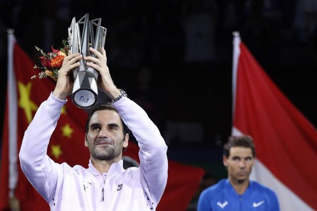 Roger Federer soulève son trophée, sous le regard... (Photo Andy Wong, AP)