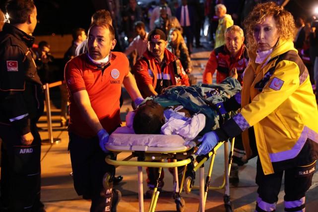 Des secouristes turcs transportent un blessé de l'attentat... (PHOTO AFP)