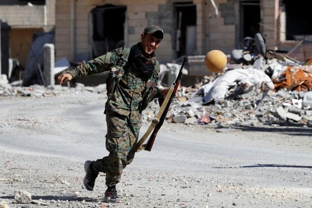Un soldat des Forces démocratiques syriennes joue au... (PHOTO REUTERS)