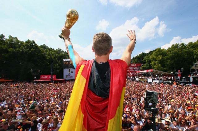 Bastian Schweinsteiger soulève et présente le trophée de... (Photo Alex Grimm, AP)