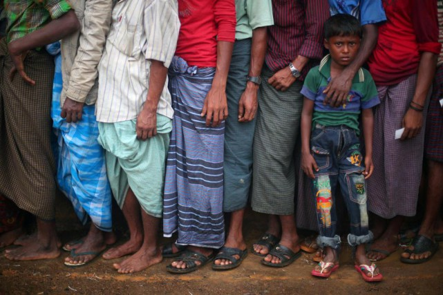 Des réfugiés rohingya attendent en file pour recevoir... (photo Hannh McKay, Reuters)