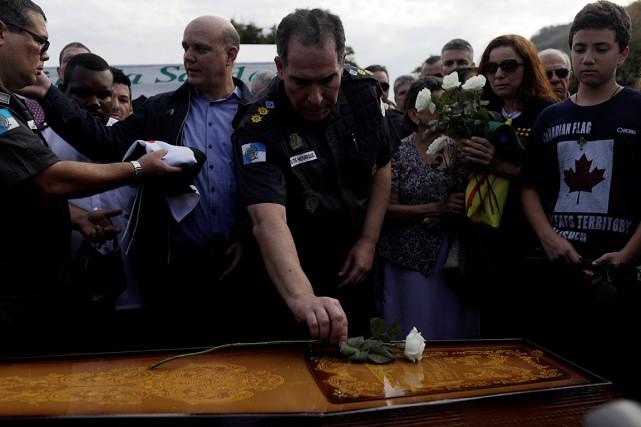Un policier dépose une fleur sur le cercueil... (PHOTO RICARDO MORAES, REUTERS)