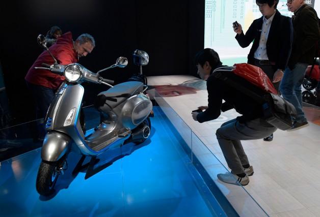 Des visiteurs examinent le scooter tout électrique Vespa... (photo AFP)