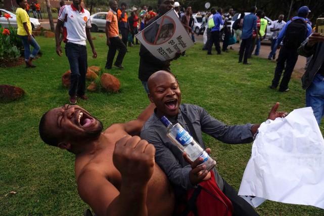 Des gens célébrent le départ de Robert Mugabe... (PHOTO AFP)