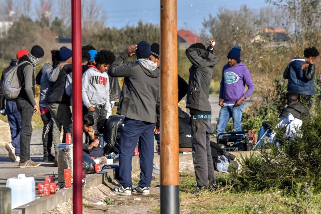 Des migrants se rassemblent dans un stationnement de... (PHOTO AFP)