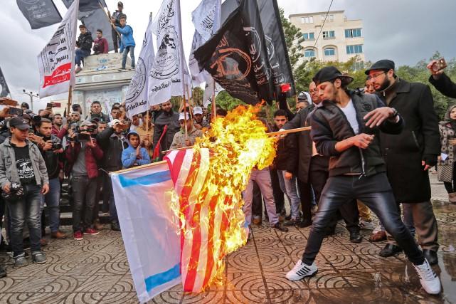 Des manifestants palestiniens brûlent les drapeaux américain et... (Photo AFP)