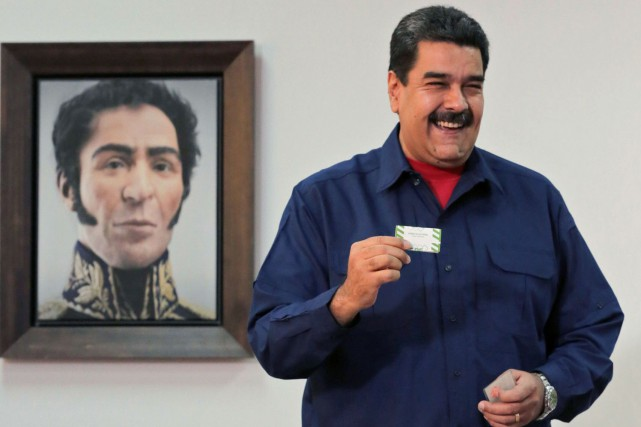 Nicolas Maduro montre son bulletin de vote dans... (PHOTO AFP)