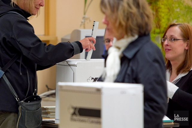 Une femme dépose son bulletin de vote lors... (PHOTO ALAIN ROBERGE, ARCHIVES LA PRESSE)