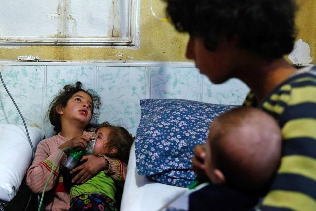 Une fillette tient un masque à oxygène sur... (PHOTO HASAN MOHAMED, AGENCE FRANCE-PRESSE)