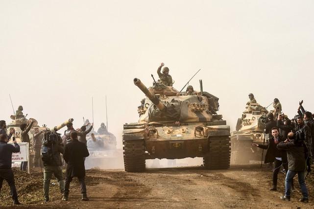 Des combattants du régime syrien passent devant des... (PHOTO BULENT KILIC, AGENCE FRANCE-PRESSE)