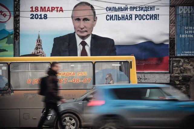 Un homme passe devant une pancarte électorale de... (PHOTO ARCHIVES AFP)
