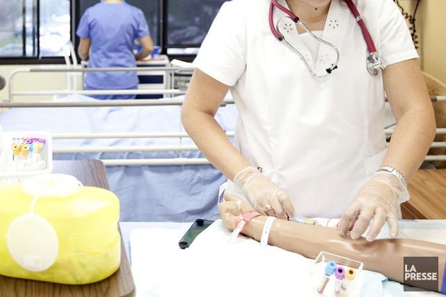 Sur cette photo, une infirmière auxiliaire reçoit une... (PHOTO MARCO CAMPANOZZI, ARCHIVES LA PRESSE)