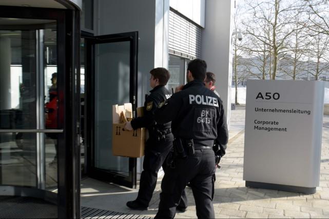 Des policiers entrent au siège social d'Audi avec... (Photo : AFP)