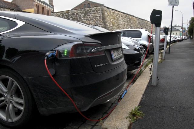 Des voitures électriques sont en recharge dans des... (photo : AFP)