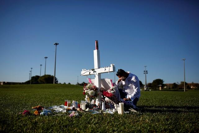 Joe Zevuloni se recueille devant une croix placée... (PHOTO CARLOS GARCIA RAWLINS, REUTERS)