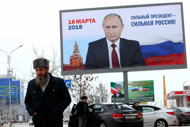 Un homme passe devant une affiche de campagne... (PHOTO MUSA SADULAYEV, ARCHIVES ASSOCIATED PRESS)