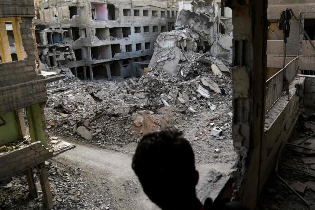 Un jeune Syrien observe la destruction provoquée par... (PHOTO AMMAR SULEIMAN, AGENCE FRANCE-PRESSE)