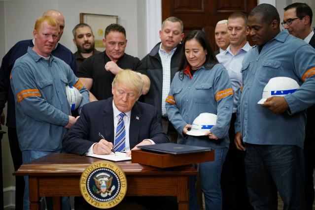 Entouré de travailleurs de l'industrie de l'acier, Donald... (PHOTO AFP)