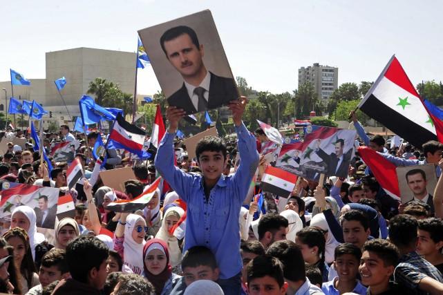 Certains participants ont brandi des drapeaux syriens, d'autres... (Photo SANA via AP)