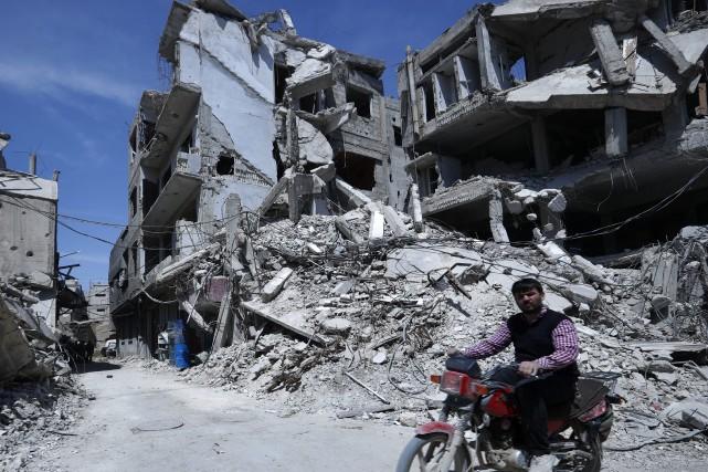 Devant des immeubles éventrés ou démolis, les habitants... (AP)
