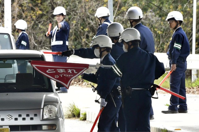 Des policiers au poste de contrôle routier de... (Photo Shingo Nishizume, Kyodo News via AP)