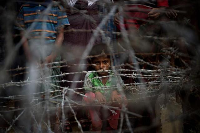 Des réfugiés rohingya sont rassemblés derrière une clôture... (PHOTO YE AUNG THU, AGENCE FRANCE-PRESSE)
