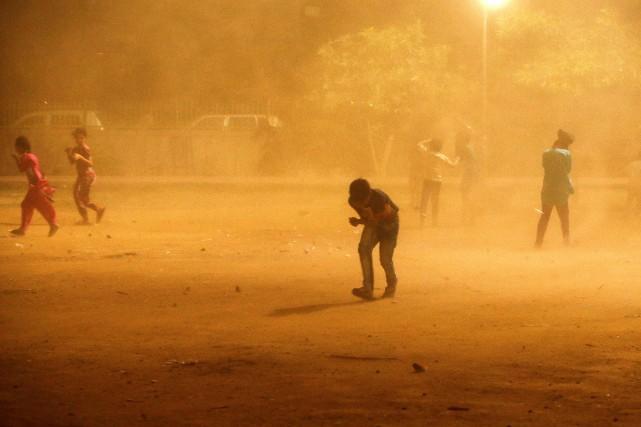 Des enfants tentent de se protéger d'une tempête... (PHOTO Adnan Abidi, REUTERS)