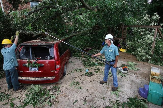 Deux hommes enlèvent un arbre qui est tombé... (PHOTO MIKE HENSDILL/THE GASTON GAZETTE VIA AP)