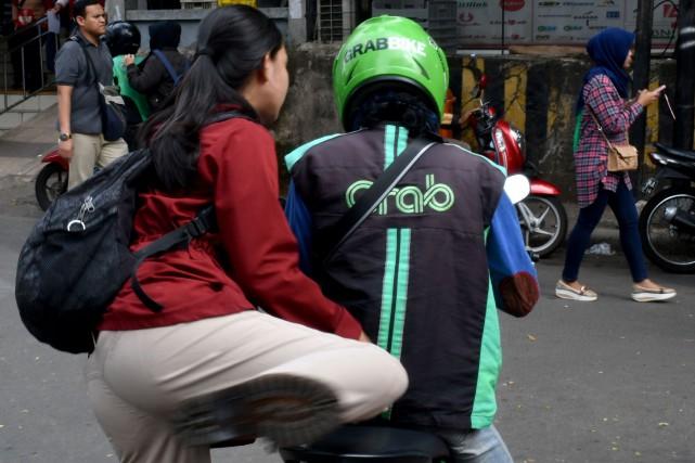 Grab a aussi un service de transport par... (photo AFP)