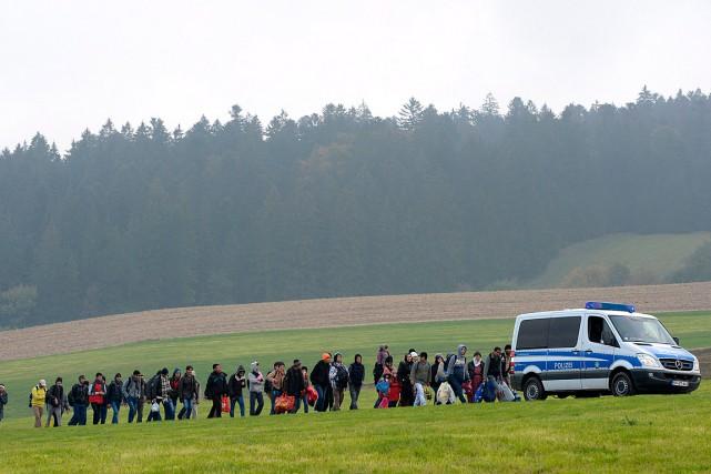 Des migrants suivent un véhicule de police après... (PHOTO CHRISTOF STACHE, ARCHIVES AGENCE FRANCE-PRESSE)