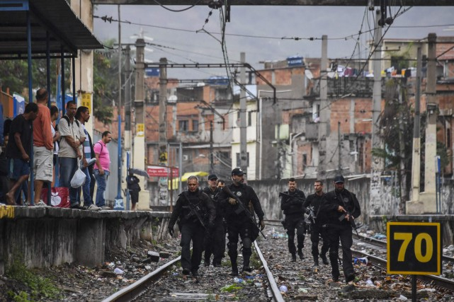 Police officers walk along train tracks during a... (PHOTO APU GOMES, ARCHIVES AGENCE FRANCE-PRESSE)