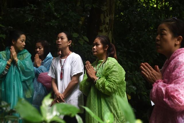 Des parents des enfants prient à l'entrée de... (AFP)