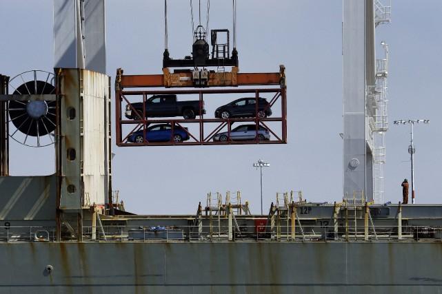 Une grue à portique chargeà bord d'un navire... (photo AP)