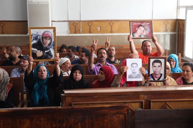 Les familles ont brandi de grandes photos des... (photo HATEM SALHI, Agence France-Presse)