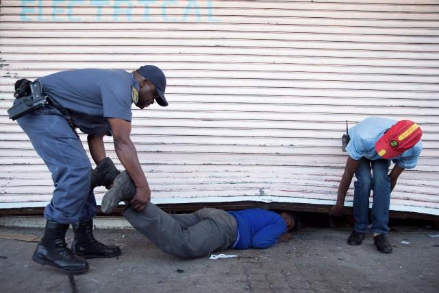 Un policier sud-africain intercepte un jeune qui tente... (Photo JAMES OATWAY, REUTERS)