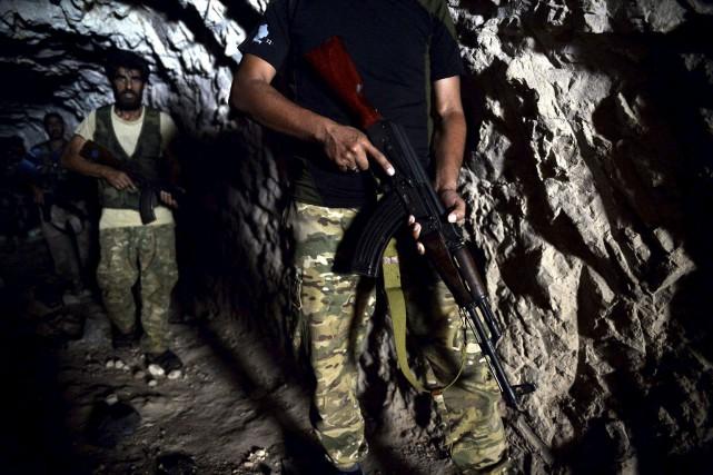 Des combattants rebelles se déplacent dans des grottes... (Photo Ugur Can, AP)