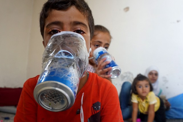 Des enfants essaient des masques à gaz de... (Photo MUHAMMAD HAJ KADOUR, AFP)