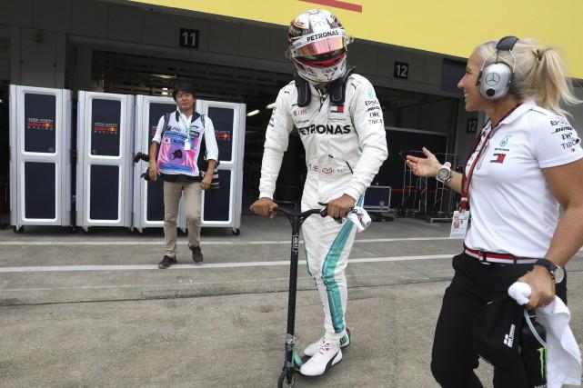 Lewis Hamilton est rentré en trottinette au paddock... (Photo Ng Han Guan, AP)