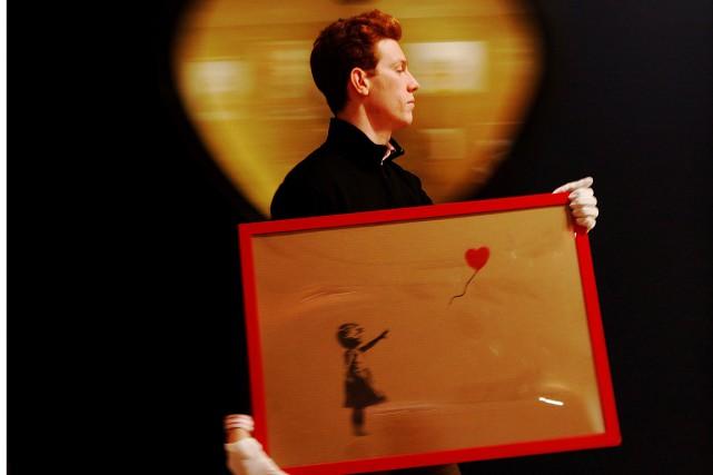 L'une des plus célèbres images de Banksy,Girl with... (Photo Luke MacGregor, archives REUTERS)