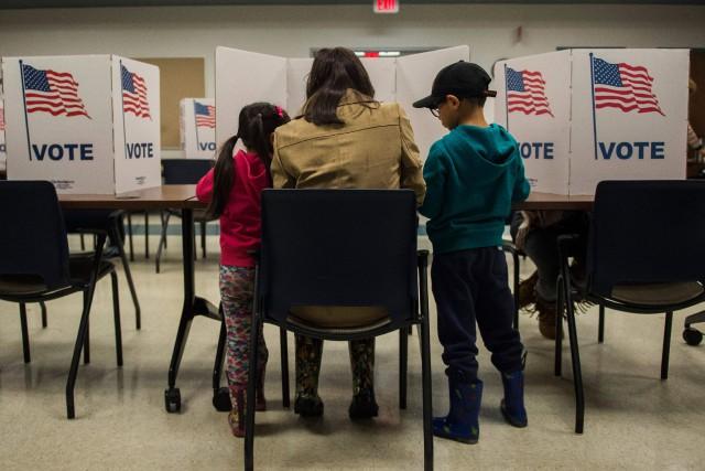 Une mère vote en compagnie de ses jeunes... (Photo ANDREW CABALLERO-REYNOLDS, AFP)