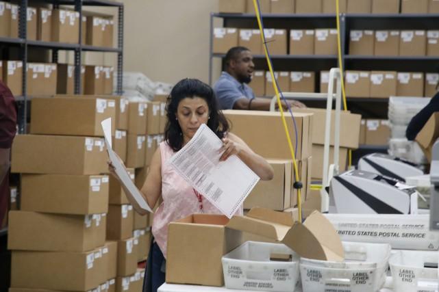 Une femme manipule des bulletins de vote provenant... (Photo Joe Skipper, Associated Press)