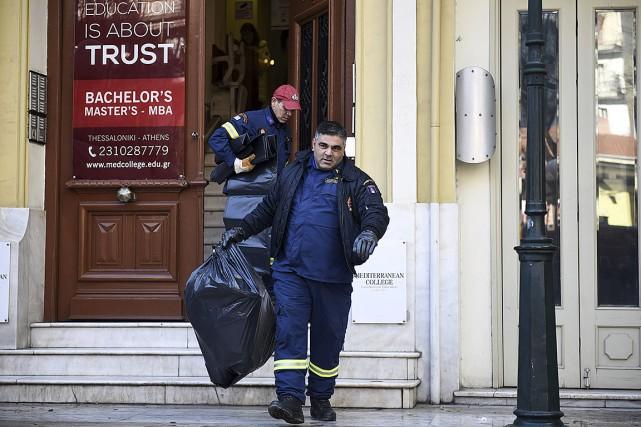 Un pompier transportant un sac de plastique quitte... (Photo Giannis Papanikos, Associated Press)