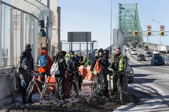 Une douzaine de cyclistes et quelques piétons ont enjambé les panneaux... (PHOTO ROBERT SKINNER, LA PRESSE)