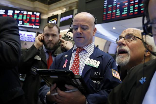 Wall Street a fini en ordre dispersé lundi, partagée entre l'optimisme autour... (Photo Richard Drew, Associated Press)